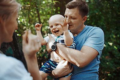 Glückliche Eltern spielen mit ihrem Baby - p1577m2280992 von zhenikeyev