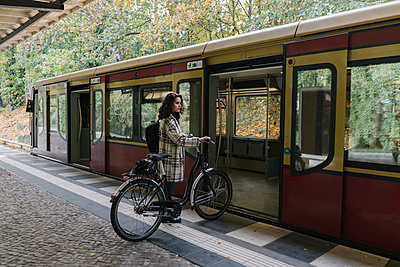 Woman with bicycle entering an underground train, Berlin, Germany - p300m2143414 by Hernandez and Sorokina