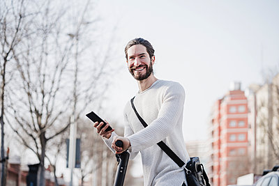 Happy male hipster holding smart phone on push scooter - p300m2274047 by Eva Blanco