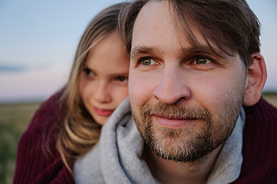 Father and daughter looking away during sunset - p300m2281800 by Ekaterina Yakunina
