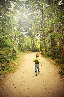 Rear View of Young Boy running down Woodland Path - p694m2200734 by Neville Mountford-Hoare