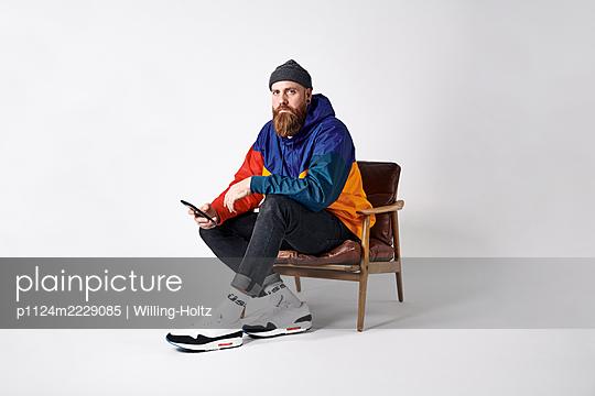 Mann in Sportdress mit Smartphone auf einem Sessel - p1124m2229085 von Willing-Holtz