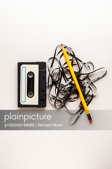 Old Audio Cassette with tape unravelling from it, and a yellow pencil, to rewind it  - p1302m2149685 by Richard Nixon