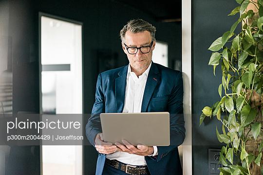 Mature businessman standing in office using laptop - p300m2004429 von Joseffson