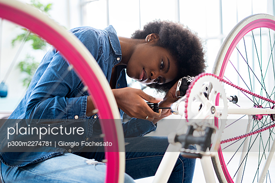 Woman repairs bike - p300m2274781 von Giorgio Fochesato