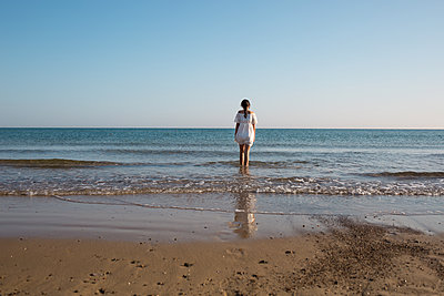 Girl standing by the sea - p1623m2290994 by Donatella Loi