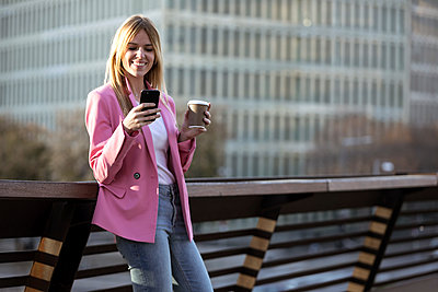 Young businesswoman using smartphone and holding coffee to go - p300m2114520 by Josep Suria