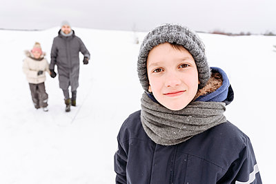 Boy standing on snow covered landscape with family in background - p300m2251430 by Ekaterina Yakunina