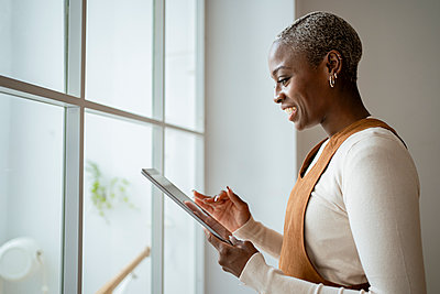 Smiling mid adult woman using digital tablet at window in living room - p300m2276373 by Rafa Cortés