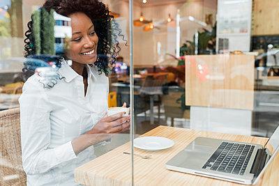 Business afro woman in coffee shop, Sevilla, Spain - p300m2299540 von Julio Rodriguez