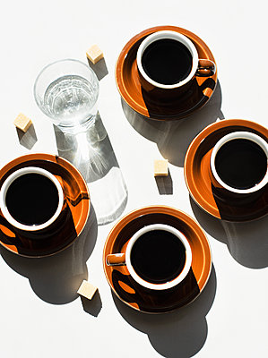 Overhead view of espresso cups and glass of water - p924m2292497 by Magdalena Niemczyk - ElanArt