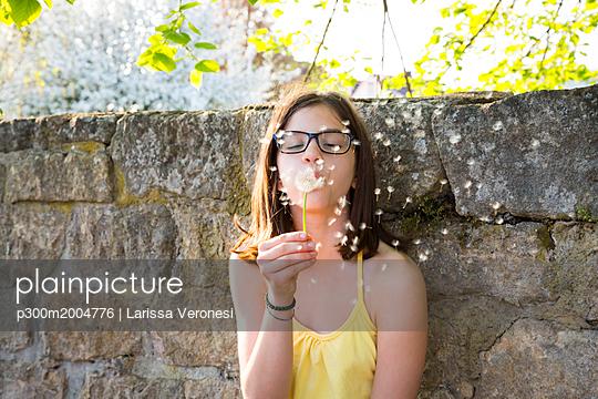 Portrait of girl blowing blowball - p300m2004776 von Larissa Veronesi
