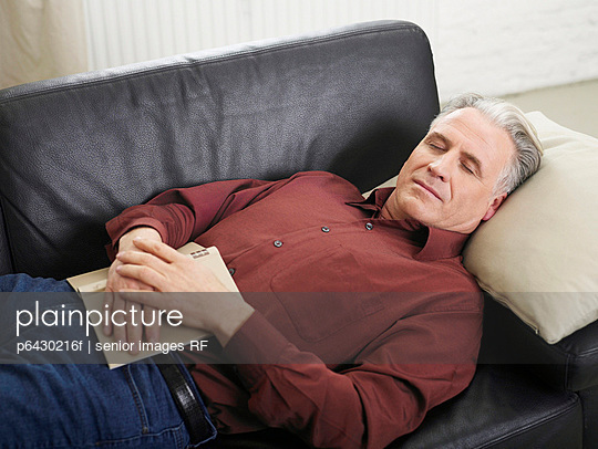 Aelterer Mann schlaeft auf dem Sofa  - p6430216f von senior images RF