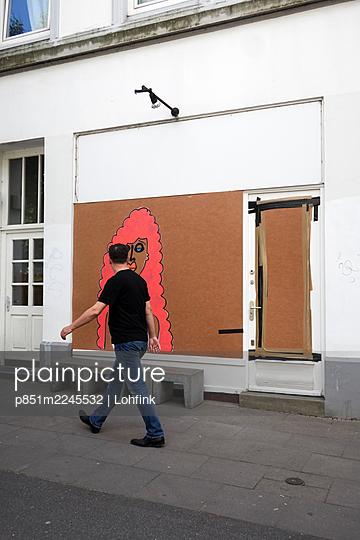 Passant vor geschlossenem Laden mit Graffiti auf Pappe - p851m2245532 von Lohfink