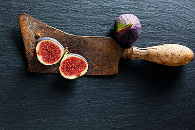 Sliced and whole fig and rusty cleaver on slate - p300m1505911 by Dieter Heinemann