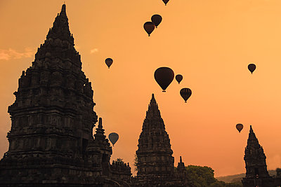Indonesia, Special Region of Yogyakarta, Silhouettes of hot air balloons flying over Prambanan temple at moody dusk - p300m2198514 by Konstantin Trubavin