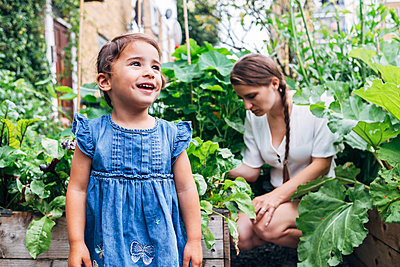 Cute girl standing at vegetable garden with woman crouching in background - p300m2293278 by Angel Santana Garcia