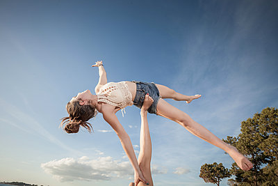 Women practising acro yoga outdoors - p429m2091218 by ROBERTO PERI
