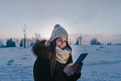 Junge Frau mit Tablet PC in Schneelandschaft - p586m2005089 von Kniel Synnatzschke
