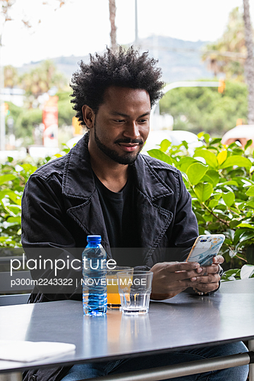 Handsome man with afro hair using mobile phone while sitting at sidewalk cafe - p300m2243322 by NOVELLIMAGE