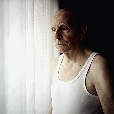 Elderly man at the window - p1092m901343 by Rolf Driesen