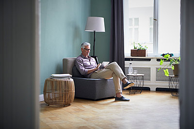 Mature man using tablet at home - p300m2030159 by Rainer Berg