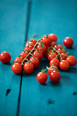 Bunch tomatoes on blue wood - p300m2121485 by Roman Märzinger