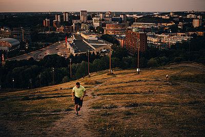 Sportsman jogging on land against city during sunset - p426m2270674 by Maskot