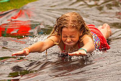 Caucasian girl sliding in water on outdoor plastic tarp - p555m1303529 by Stephen Simpson Inc