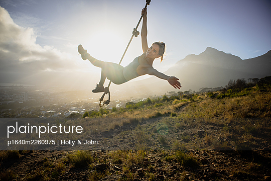 Blond woman swings on a rope, city in background - p1640m2260975 by Holly & John