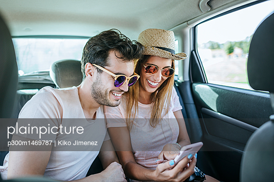 Couple in the back seat of a car looking at a cell phone - p300m1469787 by Kiko Jimenez