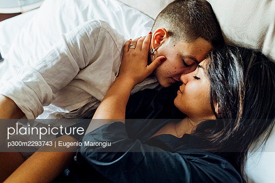 Affectionate lesbian couple romancing while lying on bed at home - p300m2293743 by Eugenio Marongiu