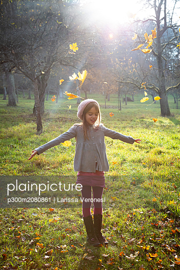 Young girl on meadow in autumn, autumn leaves - p300m2080861 by Larissa Veronesi