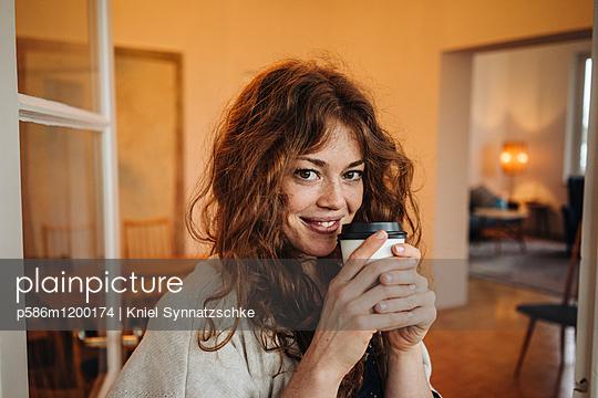 Junge Frau mit roten Haaren trinkt einen Becher Kaffee - p586m1200174 von Kniel Synnatzschke
