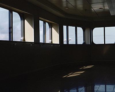 Sonnenstrahlen erhellen Tische auf einem Schiff - p1409m1465900 von margaret dearing