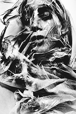 Woman's face covered with plastic wrap - p1619m2192714 by Laurent MOULAGER