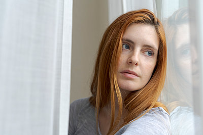 Portrait of serious young woman looking out of window - p300m2179972 by VITTA GALLERY