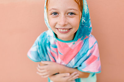 Smiling girl in bathrobe in front of beige wall - p300m2281385 by Lightsy Studio