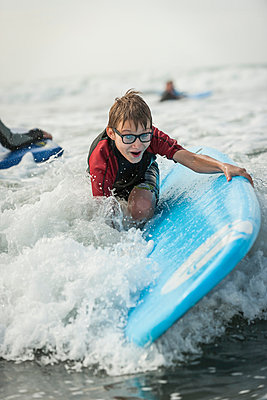 Portrait of boy learing surfboarding - p300m978826f by Andreas Pacek
