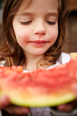Girl eating watermelon outdoors - p429m1450470 by Emma Kim