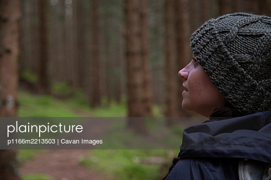 A close up shot of a person looking into the forest - p1166m2213503 by Cavan Images