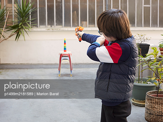 Boy playing alone in a courtyard during Covid-19 quarantine - p1499m2181589 by Marion Barat
