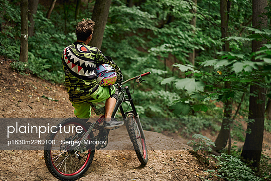 Mountainbiker looking at slope, rear view - p1630m2289100 by Sergey Mironov
