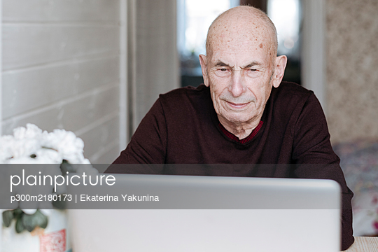 Portrait of an old man looking at laptop - p300m2180173 by Ekaterina Yakunina