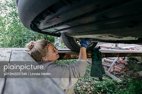 Woman repairing car - p312m2237346 by Linnéa Hådén