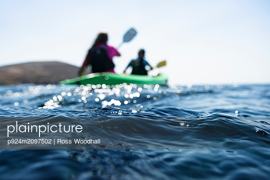 Teenage boy and mother sea kayaking, surface level shallow focus view, Limnos, Khios, Greece - p924m2097502 by Ross Woodhall