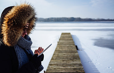 Woman with mobile phone at frozen lake - p1053m1559718 by Joern Rynio
