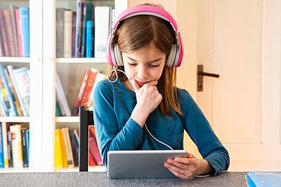 Little girl doing homework with headphones and digital tablet - p300m2104056 by Larissa Veronesi