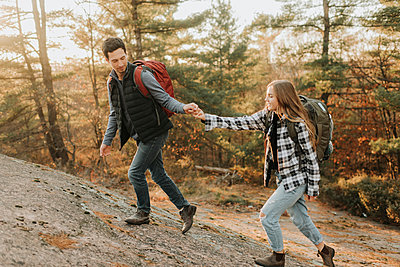Young couple holding hands while walking up hill during autumn hike - p300m2241247 by Sara Monika