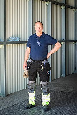 Portrait of confident senior male worker standing on warehouse entrance - p426m2018774 by Maskot